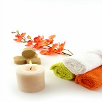 Spa towels, orchid, soap and candle on white background